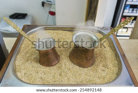 Turkish coffee prepared on hot sand for an unique taste and aroma - stock photo
