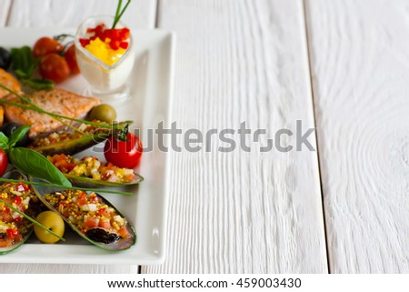 Turkish cuisine - stuffed mussels and grilled salmon on plate on white wooden background, copyspace for text. Traditional meal in Turkey restaurant - stock photo