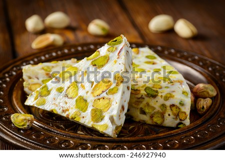 Turkish delight. Arabic dessert with and Pistachios on wooden plate. Selective focus - stock photo