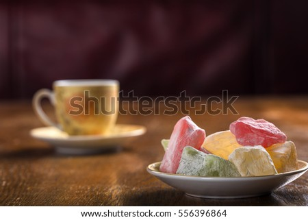Turkish delight on plate with one cup of tea in background