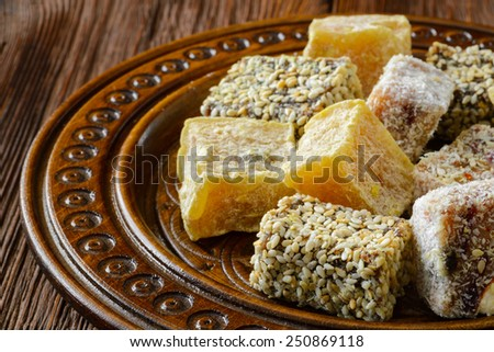 Turkish delight or rahat lokum on wooden plate. Selective focus - stock photo