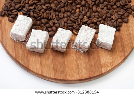 Turkish Delight with powdered sugar on a kitchen wooden board with coffee beans. - stock photo