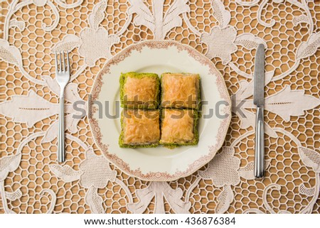 Turkish dessert baklava with pistachio on a rustic tablecloth.top view