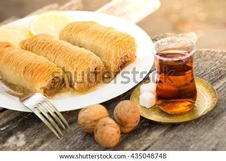 Turkish dessert Kadayif served with traditional tea on a rustic table - stock photo