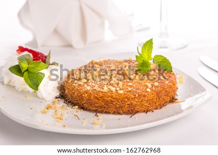 Turkish dessert kunefe with mint leaves, slices strawberry on a full fat cream and pinch of walnuts served after a nice meal - stock photo