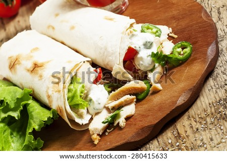 Turkish doner kebab, shawarma, roll with meat and pita bread on a wooden background, selective focus