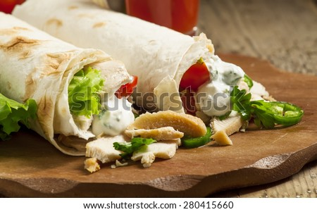 Turkish doner kebab, shawarma, roll with meat and pita bread on a wooden background, selective focus - stock photo