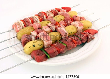 Turkish kebabs with beef, lamb, pork, onion, red and green peppers, with spicy herb potatoes on skewers, isolated on white, copy space - stock photo