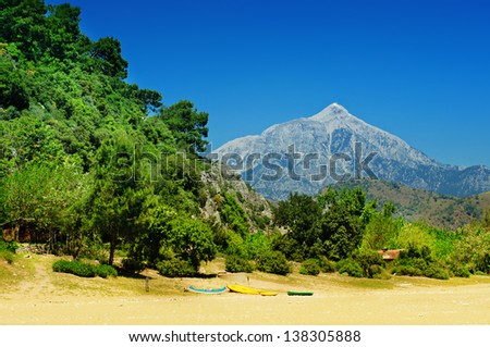 Turkish landscape with Olympos mountain, beach with boats and green forest - stock photo