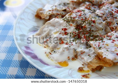 turkish manti manlama on plate with red pepper and mint on it