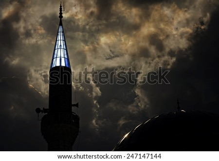 Turkish mosque at dusk with sunlight behind turret - stock photo