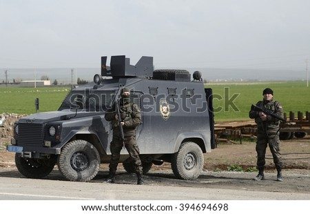 Turkish security guard checking peoples and cars at Turkey, Syria border in Sanliurfa, Turkey, 17 February 2015 - stock photo