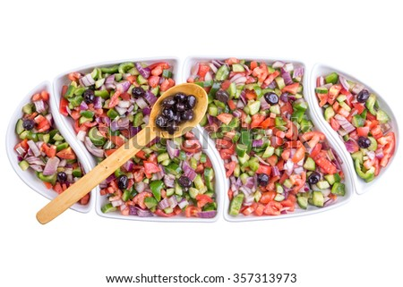 Turkish shepherd salad with colorful diced fresh vegetable served with olives in a long oval platter for a family gathering, overhead view isolated on white
