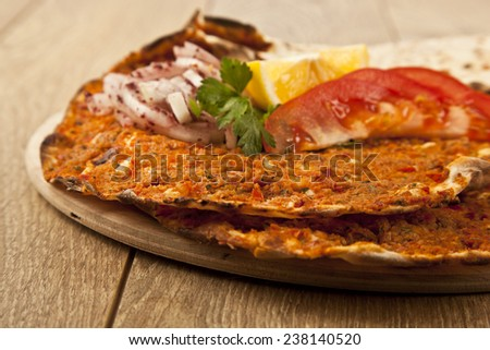 Turkish specialty pizza lahmacun pide with parsley and lemon - stock photo