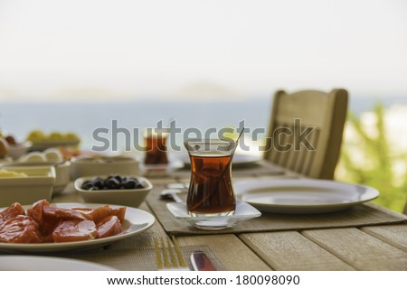 Turkish tea and a Mediterranean breakfast overlooking Greek islands and the Agean sea. / Turkish breakfast Narrow depth of field, with focus on the foreground glass of tea.  - stock photo