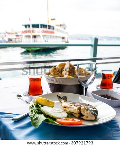 Turkish tea cup and sea bass with lemon on the background of port in Istanbul