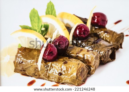 Turkish traditional food, Grape leaf dolma or yaprak sarma - stuffed with meat and rice and garnished with olives and lemon - stock photo