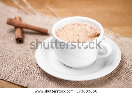 Turkish Traditional Hot Drink Sahlep witth cinnamon sticks on burlap background