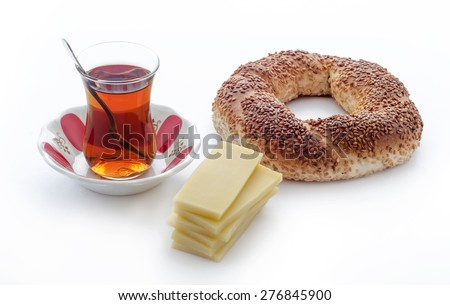 Turkish traditional sesame bagel ( Simit ) with cheddar cheese slices. And Turkish Tea. - stock photo