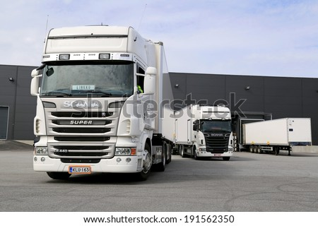TURKU, FINLAND - APRIL 26, 2014: White Scania R440 and R560 trucks unloading at a warehouse. According to Statistics Finland, 71 million tonnes of goods were transported by lorries in the Q4 of 2013. - stock photo
