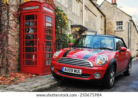 TURLEIGH - NOV 6: View of a Mini Cooper car and traditional red phone box on a village street on Nov6, 2010 in Turleigh, UK. The mini and red phone boxes are uniquely British design icons. - stock photo