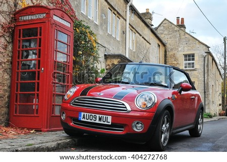 Turleigh, UK - November 6, 2010: View of a Mini Cooper car and traditional red phone box on a village street. The mini and red phone boxes are uniquely British design icons. - stock photo