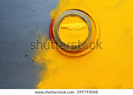 Turmeric barks and powder in vintage pot over slate background - stock photo