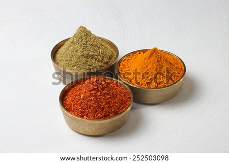 turmeric, coriander and red chilli powder in metal bowls - stock photo