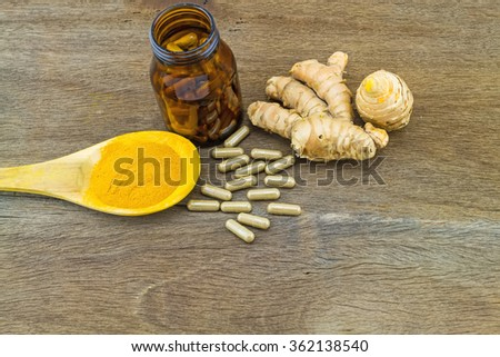 Turmeric herbal capsules in black bottle  ,fresh turmeric root  and turmeric powder in wooden spoon  on wooden  background - stock photo