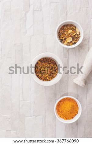 Turmeric pieces and curry. Turmeric pieces  in a mortar with pestle and curry in ceramics bowls. Top view, blank space, vintage toned image. Natural light  - stock photo