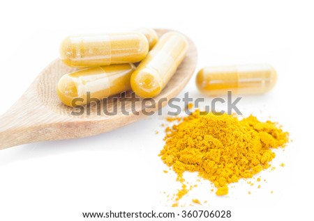 Turmeric powder and a wooden spoon with herbal capsule on white background. - stock photo