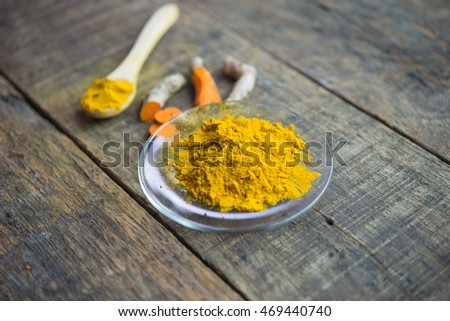 Turmeric powder and fresh roots on wooden table.