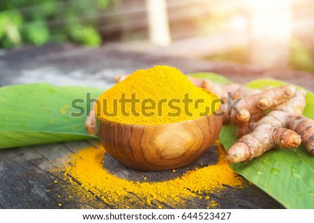 Turmeric powder and fresh turmeric in wooden bowls on old wooden table. herbal