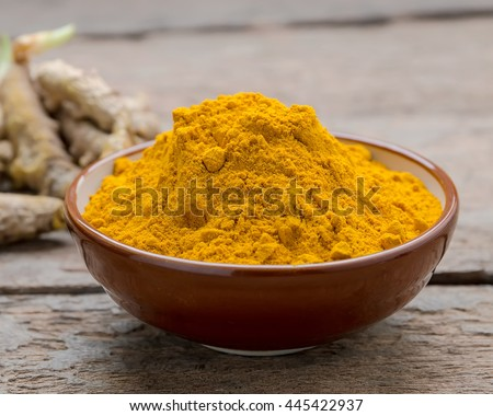Turmeric powder and fresh turmeric roots on wooden.