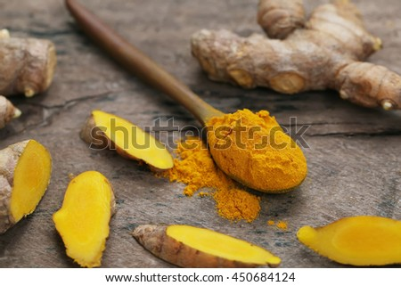 Turmeric powder and slice turmeric roots on wooden background. - stock photo