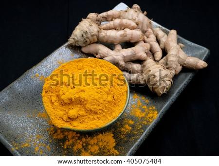 Turmeric powder and turmeric. - stock photo