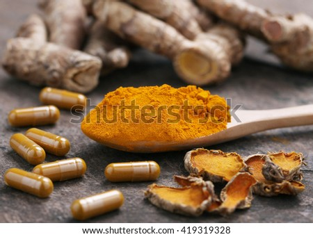 Turmeric powder and turmeric capsules on wooden background. - stock photo