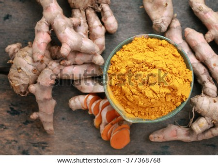 Turmeric powder and turmeric on wooden background .View from the top. - stock photo