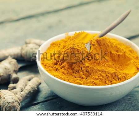 Turmeric powder and turmeric on wooden background - vintage effect style. - stock photo