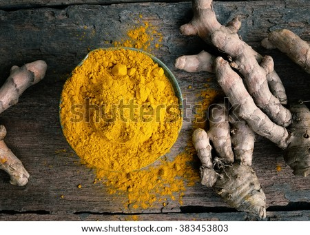 Turmeric powder and turmeric on wooden background .- Vintage Filter Processing.