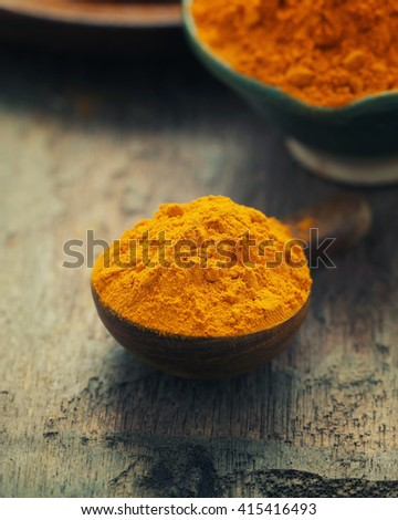 Turmeric powder and turmeric on wooden background - Vintage Filter Processing.