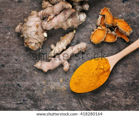 Turmeric powder and turmeric on wooden background - Vintage Filter Processing. - stock photo