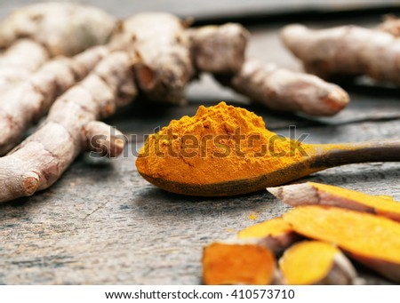 Turmeric powder and turmeric on wooden spoon.