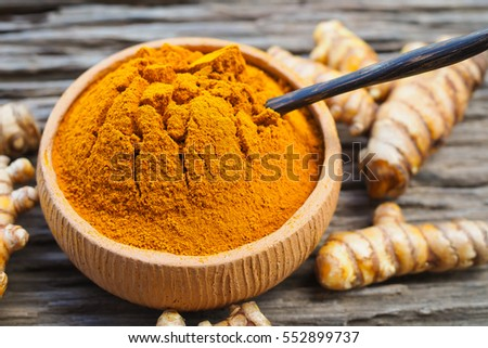 Turmeric powder in bowls and fresh turmeric on old wooden background. herbal