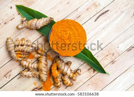 Turmeric powder in bowls on wooden table. herbal