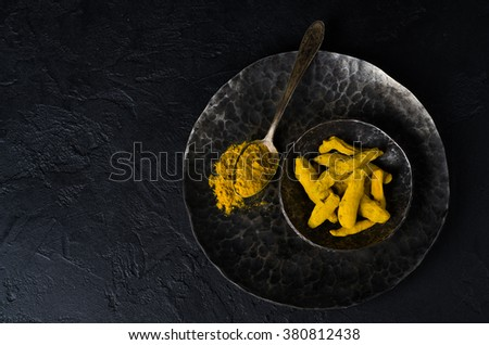 Turmeric powder in  iron vintage spoon with turmeric sticks in black iron bowl on dark stone background. Selective focus - stock photo