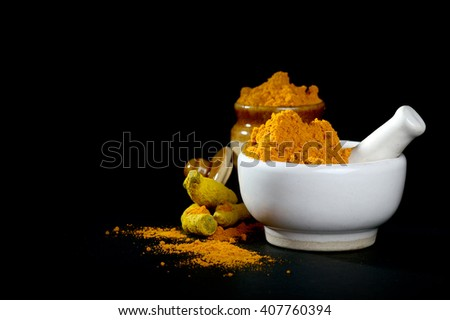 Turmeric powder in mortar with pestle and roots with clay pot on black background - stock photo