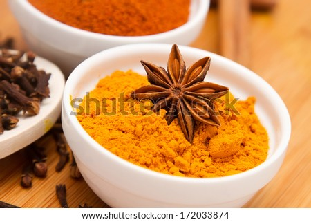 Turmeric powder in white bowl with anise flower on top, on wooden background - stock photo