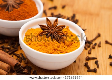 Turmeric powder in white bowl with anise flower on top, on wooden table background - stock photo