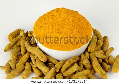 Turmeric powder in white bowl with turmeric sticks. - stock photo